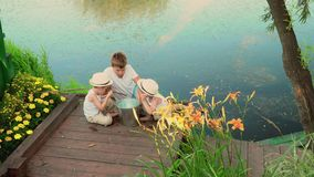Brothers are whispered after fishing. happy children after fishing. Children watch a catch after fishing stock video