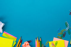 Bürotischschreibtisch mit Satz bunten Versorgungen, weißer leerer Notizblock, Schale, Stift, PC, zerknitterte Papier, Blume auf B Stockfotografie
