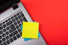 Bürotischschreibtisch mit Satz bunten Versorgungen, weißer leerer Notizblock, Schale, Stift, PC, zerknitterte Papier, Blume auf R Lizenzfreie Stockbilder