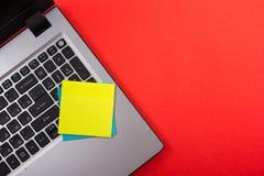 Bürotischschreibtisch mit Satz bunten Versorgungen, weißer leerer Notizblock, Schale, Stift, PC, zerknitterte Papier, Blume auf R Stockfotografie