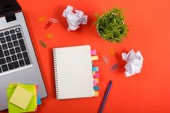 Bürotischschreibtisch mit Satz bunten Versorgungen, weißer leerer Notizblock, Schale, Stift, PC, zerknitterte Papier, Blume auf R Stockbild