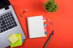 Bürotischschreibtisch mit Satz bunten Versorgungen, weißer leerer Notizblock, Schale, Stift, PC, zerknitterte Papier, Blume auf R Stockfoto