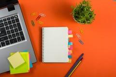 Bürotischschreibtisch mit Satz bunten Versorgungen, weißer leerer Notizblock, Schale, Stift, PC, zerknitterte Papier, Blume auf R Stockfotos