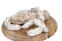 Brotlaib mit Würsten auf hölzerner Platte Stockfotografie