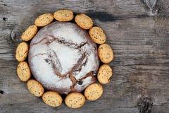 Brotlaib und bisquits auf altem Holztisch Stockbild