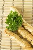 Brotstöcke mit Petersilie auf einem hölzernen Stand Lizenzfreies Stockfoto