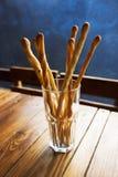 Brotstöcke mit Samen des indischen Sesams in einer Glasschale sind auf dem Tisch in einem Café Stockfoto