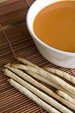 Brotsteuerknüppel und Tomatesuppe Stockfotografie