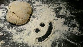 Brotteig mit einem smileygesicht im Mehl stockfotos