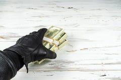 Brotts- begreppsman i svarta läderhandskar som rymmer tegelstenar av pengar royaltyfri bild