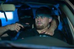 Brottslig man som pekar ett vapen på den förskräckta chauffören royaltyfri foto