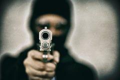 Brottslig rånare med att sikta vapnet, skurk i huv arkivbilder