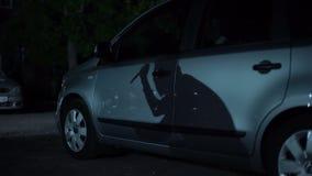 Brottslig skugga med kniven i handen som reflekterar på parkerad bilyttersida, bilkapning lager videofilmer