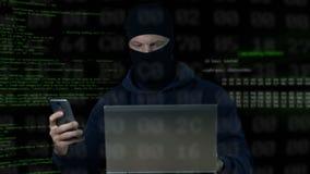 Brottsling i maskering som kontrollerar bevakningkameran på bärbara datorn och telefonen, databas stock video