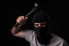 Brottsling i T-tröja och balaclava med hammaren royaltyfria foton