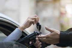 Brottsling med vapnet som rånar kvinnan i bil arkivbild