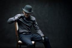 Brottslingen och rånaren i svarta handskar sitter på en stol royaltyfri fotografi