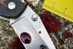 Brottsplatsutredning, blodig kniv med brottsliga markörer på jordning, mordtecken royaltyfria bilder