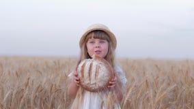 Brotzüchter-Kindermädchen, kleine angemessene behaarte Landwirttochter beißt geschmackvolles gebackenes Brot und das Lächeln, die stock video