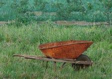 Brouette rouillée dans l'herbe grande Images libres de droits