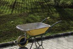 Brouette simple près de l'herbe couverte par l'engrais Photo stock