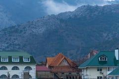 Brouillard au-dessus des montagnes et des maisons photos stock