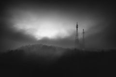 Brouillard brumeux au-dessus de la connexion et tour hertzienne dans la montagne Photos stock