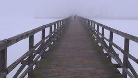 Brouillard de matin sur le pont en bois et un écolier de marche clips vidéos