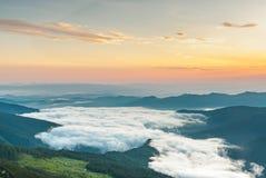 Brouillard en montagnes sur le coucher du soleil photographie stock libre de droits