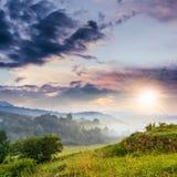 Brouillard froid sur le coucher du soleil chaud en montagnes images libres de droits