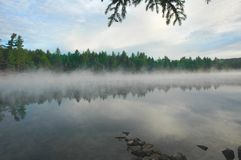 Brouillard se levant d'un lac dans la région sauvage Images stock