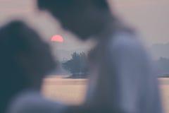 Brouillez la scène affectueuse de baiser de silhouette de couples avec le coucher du soleil Images stock