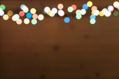 Brouillez le fond et le bokeh du pensionnaire de lumière de Noël sur le fond en bois Photos stock