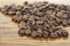 Broun coffee beans isolated on brown wooden texture background royalty free stock image