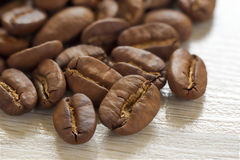 Broun coffee beans on textured wooden background with. Shallow depth of field stock images