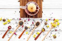 Brouw de aromatische thee Theepot dichtbij houten lepels met droge theebladen, bloemen en kruiden op witte houten achtergrond stock foto's