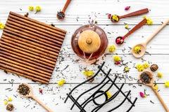 Brouw de aromatische thee Theepot dichtbij houten lepels met droge theebladen, bloemen en kruiden op witte houten achtergrond royalty-vrije stock foto