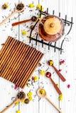 Brouw de aromatische thee Theepot dichtbij houten lepels met droge theebladen, bloemen en kruiden op witte houten achtergrond stock afbeeldingen