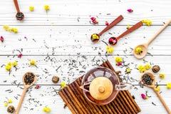 Brouw de aromatische thee Theepot dichtbij houten lepels met droge theebladen, bloemen en kruiden op witte houten achtergrond royalty-vrije stock fotografie