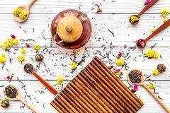 Brouw de aromatische thee Theepot dichtbij houten lepels met droge theebladen, bloemen en kruiden op witte houten achtergrond stock afbeelding