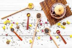 Brouw de aromatische thee Theepot dichtbij houten lepels met droge theebladen, bloemen en kruiden op witte houten achtergrond royalty-vrije stock afbeelding