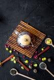 Brouw de aromatische thee Theepot dichtbij houten lepels met droge theebladen, bloemen en kruiden op zwarte houten achtergrond royalty-vrije stock afbeelding
