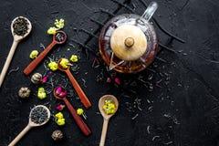 Brouw de aromatische thee Theepot dichtbij houten lepels met droge theebladen, bloemen en kruiden op zwarte houten achtergrond stock afbeelding