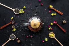 Brouw de aromatische thee Theepot dichtbij houten lepels met droge theebladen, bloemen en kruiden op zwarte houten achtergrond stock foto's