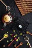 Brouw de aromatische thee Theepot dichtbij houten lepels met droge theebladen, bloemen en kruiden op zwarte houten achtergrond stock foto
