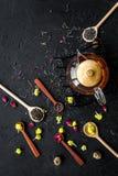 Brouw de aromatische thee Theepot dichtbij houten lepels met droge theebladen, bloemen en kruiden op zwarte houten achtergrond royalty-vrije stock foto's