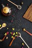 Brouw de aromatische thee Theepot dichtbij houten lepels met droge theebladen, bloemen en kruiden op zwarte houten achtergrond royalty-vrije stock fotografie