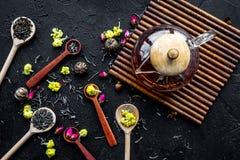 Brouw de aromatische thee Theepot dichtbij houten lepels met droge theebladen, bloemen en kruiden op zwarte houten achtergrond stock fotografie