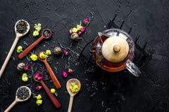 Brouw de aromatische thee Theepot dichtbij houten lepels met droge theebladen, bloemen en kruiden op zwarte houten achtergrond stock afbeeldingen
