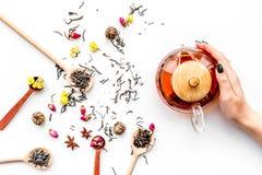 Brouw thee met bloemen en kruiden De theepot van de handgreep op witte hoogste mening als achtergrond royalty-vrije stock afbeeldingen
